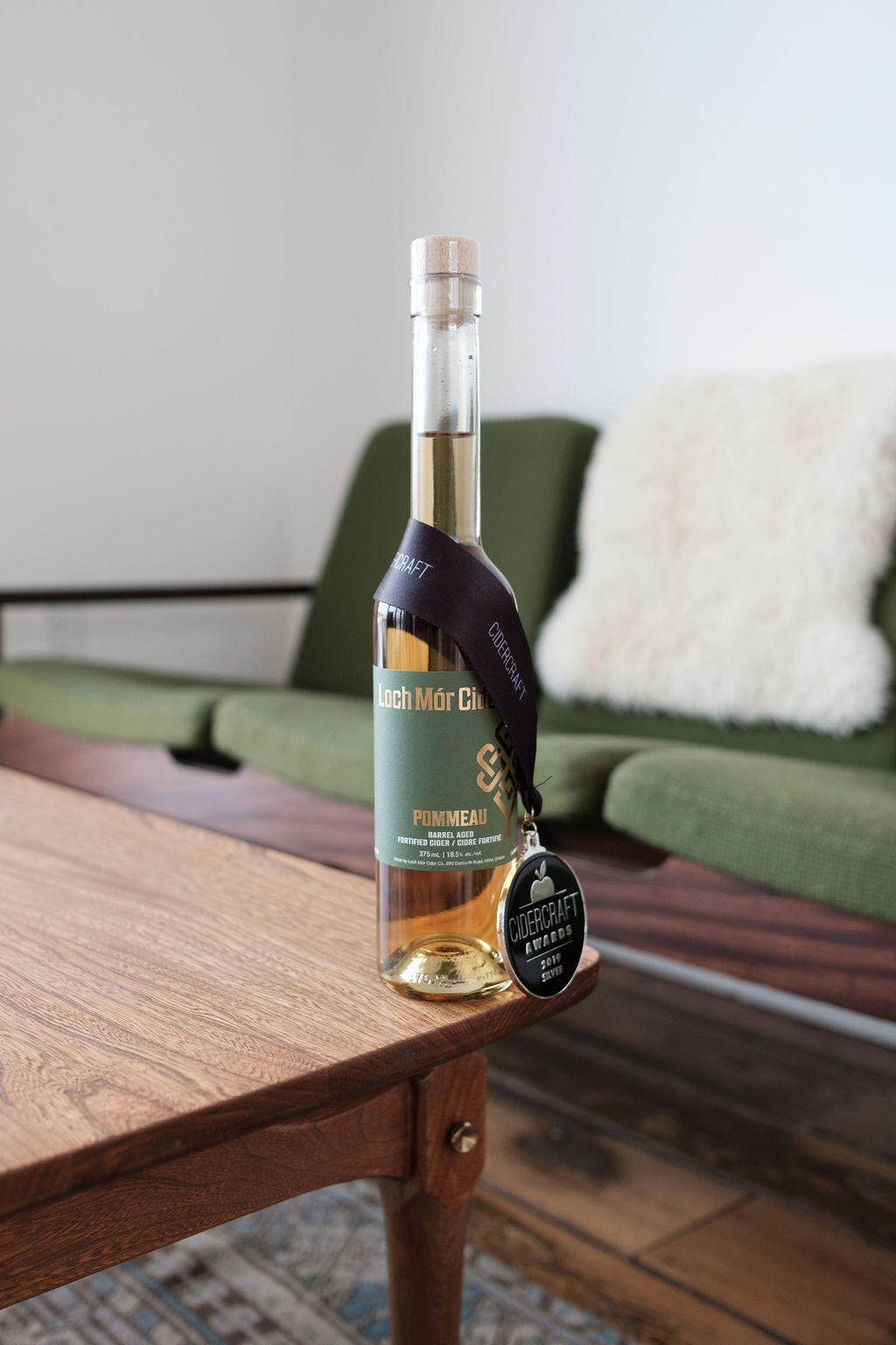 Loch Mor Cider Pommeau bottle with silver cidercraft award medal around neck, sitting on a table in the tasting room in prince edward county, ontario canada