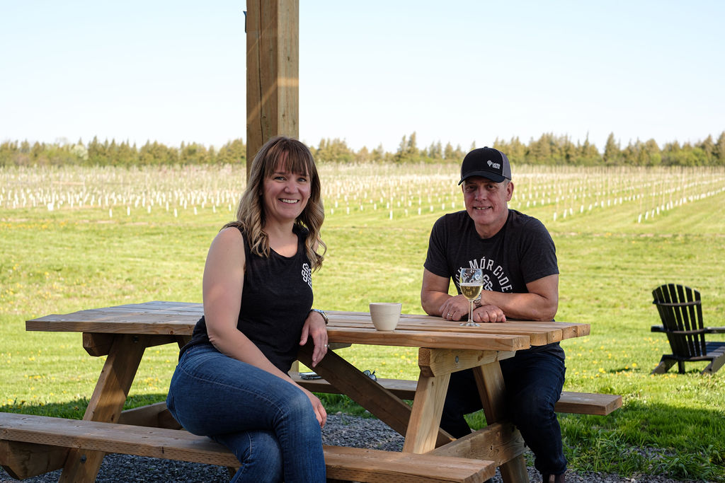 Gary & Sara cidermakers and orchardists sitting at table overlooking orchard enjoying cider