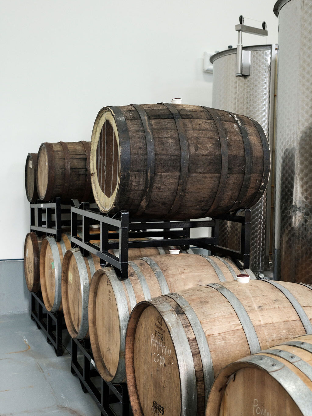 wine barrels and stainless tanks fermenting and ageing cider
